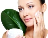 6511746-attractive-woman-applying-moisturizer-cream-on-her-cheek-and-fresh-leaf-close-her-face